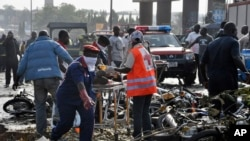 Rescue workers work to recover victims at the site of a blast near Abuja, Nigeria, April 14, 2014.