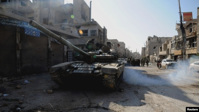 Soldiers loyal to Syria's President Bashar al-Assad are seen at Hujaira town, south of Damascus, after the soldiers took control of it from the rebel fighters, in this handout photograph distributed by Syria's national news agency SANA, Nov. 13, 2013.