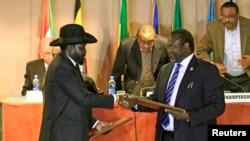 1일 남수단의 살바 키르 대통령(왼쪽)과 반군 지도자 리에크 마차르가 내전을 끝내기로 약속하는 내용의 평화 합의안에 서명한 후 합의안을 교환하고 있다.