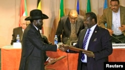FILE - South Sudan's President Salva Kiir, left, and South Sudan's rebel commander Riek Machar exchange documents after signing a cease-fire agreement during an Inter Governmental Authority on Development (IGAD) Summit in Addis Ababa, Ethiopia.