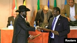 FILE - South Sudan's President Salva Kiir (L) and rebel commander Riek Machar exchange documents after signing a cease-fire agreement in Ethiopia's capital Addis Ababa, Feb. 1, 2015.