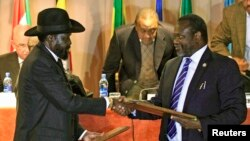 FILE - South Sudan's President Salva Kiir, left, and rebel commander Riek Machar exchange documents after signing a cease-fire agreement in Addis Ababa, Ethiopia, Feb. 1, 2015.