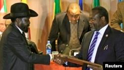 ARCHIVES-Le président du Soudan du Sud, Salva Kiir (à gauche) se salue avec son ancien Premier ministre devenu chef rebelle, Riek Machar