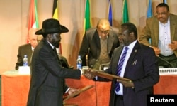 FILE - South Sudan's President Salva Kiir, left, and South Sudan rebel commander Riek Machar exchange documents after signing a cease-fire agreement during the Inter Governmental Authority on Development (IGAD) Summit on the case of South Sudan in Ethiopia.