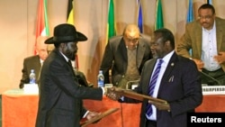 The South Sudan government announced on Friday, Aug. 14, 2015, that President Salva Kiir (L), shown here exchanging an earlier peace deal with rebel leader Riek Machar, will not travel to Addis Ababa to attend the latest round of talks to bring peace to his country.