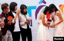 FILE - Newly married same-sex couple Tran Ngoc Diem Hang (R) and Le Thuy Linh (2nd R) share a moment during their public wedding as part of a lesbian, gay, bisexual, and transgender (LGBT) event on a street in Hanoi, October 27, 2013.