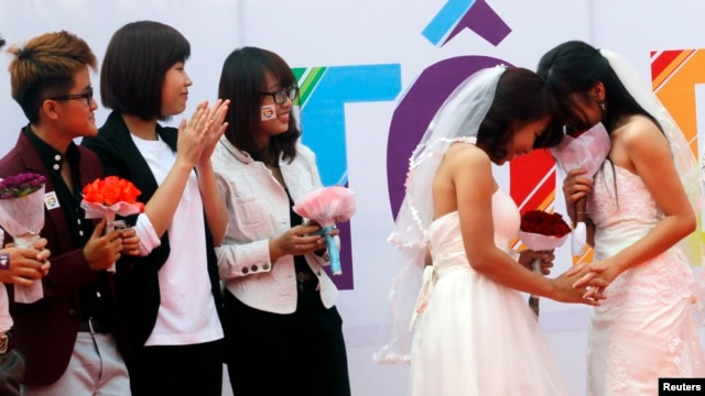 FILE - Newly married same-sex couple Tran Ngoc Diem Hang (R) and Le Thuy Linh (2nd R) share a moment during their public wedding as part of a lesbian, gay, bisexual, and transgender event on a street in Hanoi, October 27, 2013.