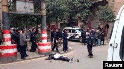 A body is pictured lying on the ground at a crime scene on a street, in Changsha, Hunan Province March 14, 2014.