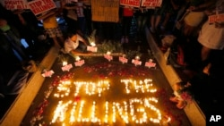 """FILE - Human rights activists light candles for the victims of extrajudicial killings around the country in the wake of the """"war on drugs"""" campaign by Philippine President Rodrigo Duterte in suburban Quezon city northeast of Manila, Philippines."""
