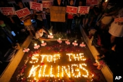 "FILE - Human rights activists light candles for the victims of extrajudicial killings around the country in the wake of the ""War on Drugs"" campaign waged by Philippine President Rodrigo Duterte, in suburban Quezon city northeast of Manila, Philippines, Aug. 15, 2016."