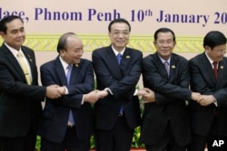 China's Premier Li Keqiang, center, shakes hands with his counterpart, Nguyen Xuan Phuc, second from left, of Vietnam, Prayuth Chan-o-cha, left, prime minister of Thailand, Hun Sen, second from right, of Cambodia, and Thongloun Sisolith, right, of Laos, before an opening of the Lancang-Mekong Cooperation Leaders' Meeting, in Phnom Penh, Cambodia, Jan. 10, 2018.