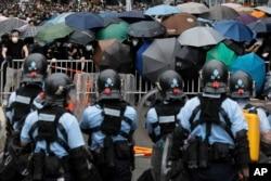2019年6月12日在香港立法会附近,带有防暴装备的警察同打着雨伞的示威者对峙。