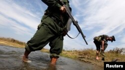 A soldier from the Kachin Independence Army puts on his shoes as he and his comrade cross a stream towards the front line in Laiza, Kachin state, January 29, 2013.