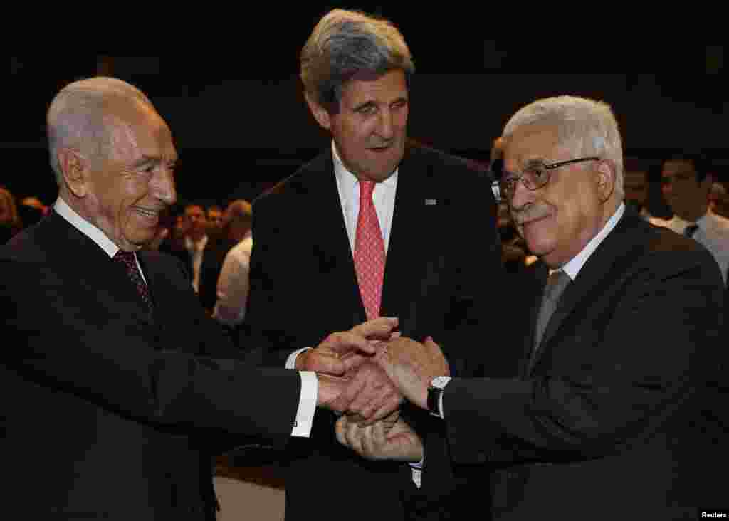 U.S. Secretary of State John Kerry (C) shakes hands with Israeli President Shimon Peres (L) and Palestinian President Mahmoud Abbas at the World Economic Forum at the King Hussein Convention Center, at the Dead Sea, Jordan.