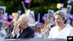 Former Cambodian King Norodom Sihanouk and Queen Norodom Monineath Sihanouk are greeted by students along a Phnom Penh road during during the marking of the country's 50th Independence Day in 2003.