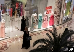 FILE - a shopper strolls through a mall in Riyadh, Saudi Arabia, April 15, 2015.