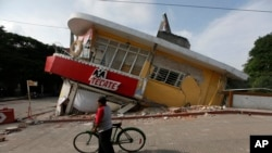 FILE - A man walks his bike past a building felled by a 7.1 earthquake in Jojutla, Morelos state, Mexico, Sept. 20, 2017.