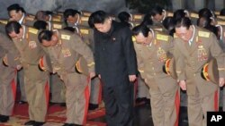 In this Saturday, Dec. 24, 2011 photo released by the Korean Central News Agency and distributed in Tokyo, Sunday, Dec. 25, 2011, by the Korea News Service, Kim Jong Un, center, North Korean leader Kim Jong Il's youngest known son and successor, visits at