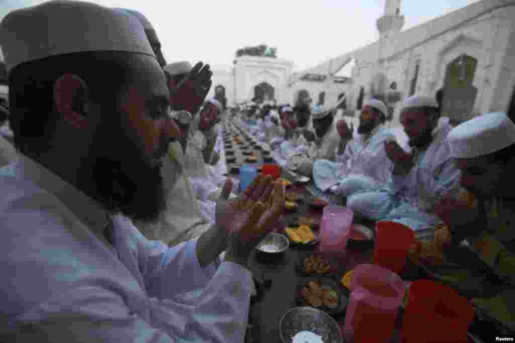 Men pray before breaking their fast on the first day of Ramadan, the holiest month in the Islamic calendar, at a mosque in Peshawar, Pakistan, June 29, 2014.