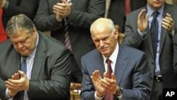 ນາຍົກລັດຖະມົນຕີກຣີສ George Papandreou (ຂວາ) ສະແດງ ຄວາມຍິນດີຫລັງຈາກຊະນະລົງຄະແນນສຽງບໍ່ໄວ້ວາງໃຈໃນສະພາ