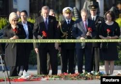 Turkish President Recep Tayyip Erdogan, second from left, and his wife, Emine Erdogan, left, hold carnations during a commemoration for the victims of Saturday's bombings in Ankara, Oct. 14, 2015.