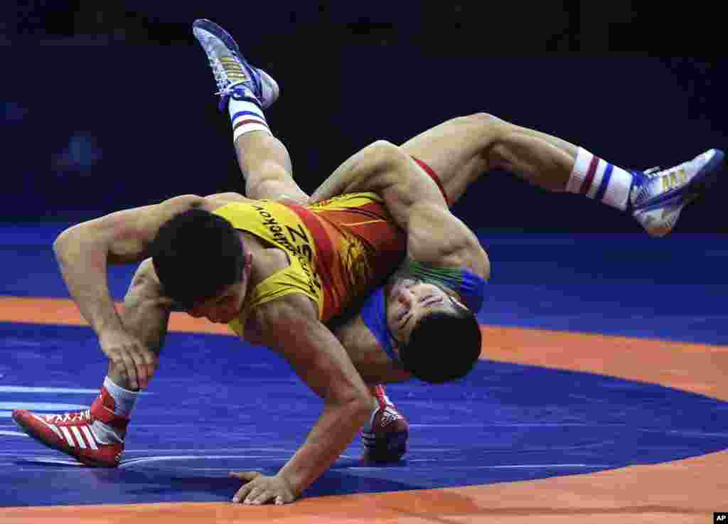 Eldaniz Azizli of Azerbaijan, right, battles Zholaman Sharshenbekov of Kyrgyzstan, left, in the  Greco-Roman 55kg category of the Wrestling World Championships in Budapest.