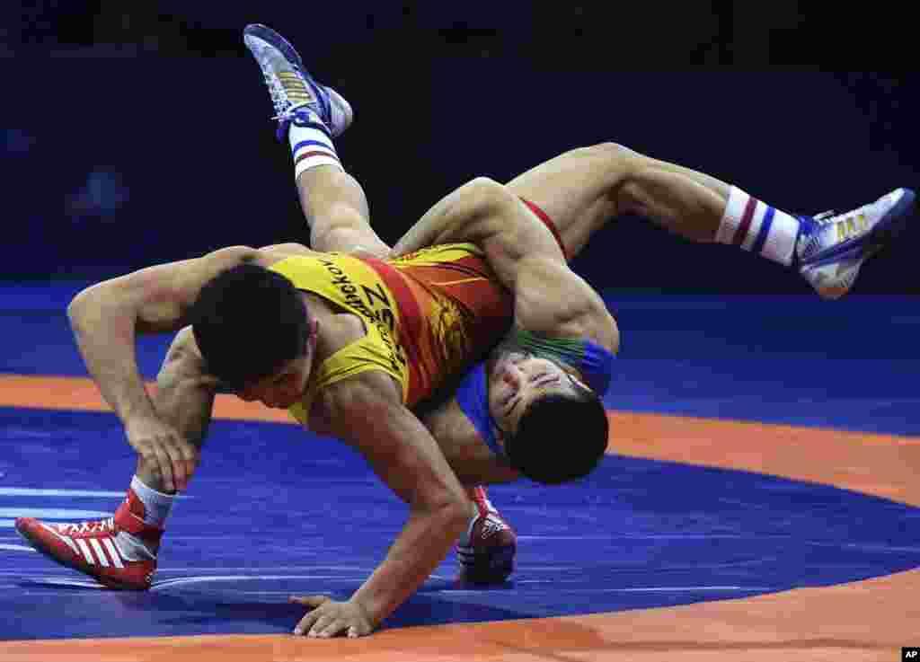 Eldaniz Azizli of Azerbaijan, right, battles Zholaman Sharshenbekov of Kyrgyzstan, left, in the Greco-Roman 55kg category of the Wrestling World Championships in Budapest.