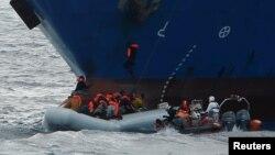 Des migrants s'approchent d'un bateau de secours de l'ONG Migrant Offshore Aid Station, dans les eaux internationales de la Méditerranée au large de la Libye, le 16 avril 2017.