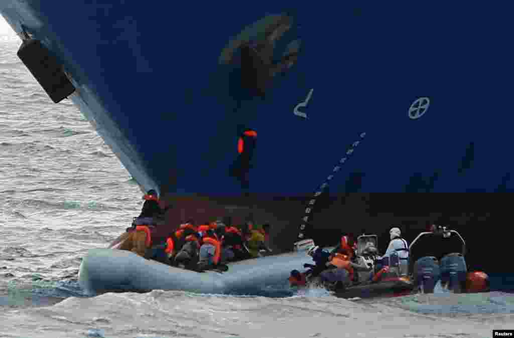 Migrants in a rubber dinghy fall into the sea alongside a rigid hulled inflatable boat of the Malta-based NGO Migrant Offshore Aid Station, as a migrant climbs onto the anchor of the Panama-registered ship Tuna 1 and one hangs onto its bow, after some 20 migrants on another rubber dinghy drowned in the central Mediterranean in international waters off the coast of Libya.