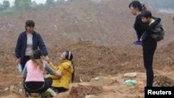 Phụ nữ có thân nhân mất tích ngồi khóc tại hiện trường vụ đất chuồi ở Trung Quốc.