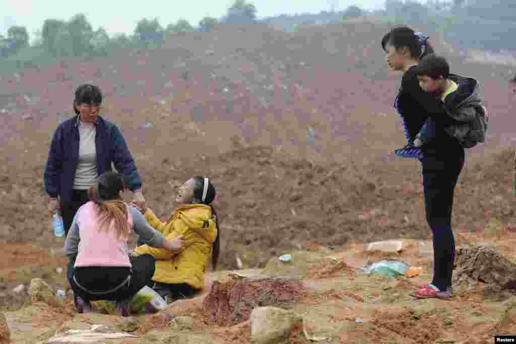 A woman (3rd L), who is a relative of several missing people, cries at the site of a landslide that hit an industrial park in Shenzhen, Guangdong province, China. More than 70 people are still missing.