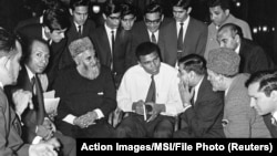 "FILE - Muhammad Ali speaks to Muslims holding a book called ""Towards Understanding Islam"" written by Sayyid Abul Ala Maududi in London, May 1966. Ali died in Phoenix, Arizona, June 3, 2016."