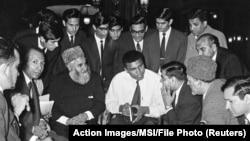 Muhammed Ali 1966'ta Londra'da Müslümanlarla sohbet ederken. Elindeki Ebu'l Ala Mevdudi'nin İslam'ı Anlamaya Doğru kitabı var