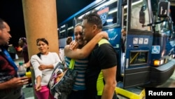 FILE - Cuban migrant Mailin Perez is greeted by her husband, Jose Caballero, after arriving at a bus station in Texas, via Mexico, in this 2014 photo.