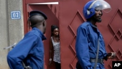 FILE - A resident looks out of house as riot police walk past in Bujumbura's Nyakabiga district in Burundi, May 4, 2015.