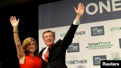 John Tory waves with his wife Barbara Hackett after being elected as mayor in Toronto, Oct. 27, 2014.