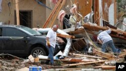Joe Curry, left, and his friend search the damaged remains of his home.