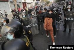 Agentes vestidos de civil detienen a una mujer durante las protestas tras el juicio político al presidente Martín Vizcarra, en Lima