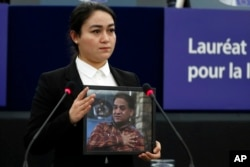 Jewher Ilham, daughter of imprisoned Uighur scholar Ilham Tohti holds a photo of her father during the Sakharov Prize ceremony at the European Parliament, in Strasbourg, eastern France, Wednesday, Dec. 18, 2019.