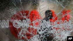 A security guard walks behind shattered glass at the CNN building at the CNN Center in the aftermath of a demonstration against police violence on May 30, 2020, in Atlanta.