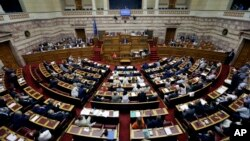 FILE - Greece's Prime Minister Alexis Tsipras delivers a speech during an emergency parliament session in Athens, July 23, 2015