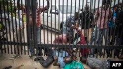 Burundian students slide under the main access gate of the American Embassy in Bujumbura, June 25, 2015.