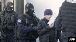 Спецпризначенці супроводжують затриманого співробітника КПП на кордоні між Румунією та Сербією.