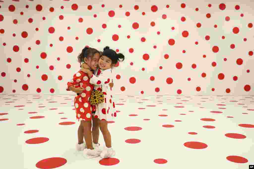 "Wearing matching dresses, Takara Thomas, 3, left, and Noemi Vega, 4, hug in a polka-dotted room created by Japanese artist Yayoi Kusama, part of the installation called ""With All My Love for the Tulips, I Pray Forever"" at the Marciano Art Foundation in Los Angeles."