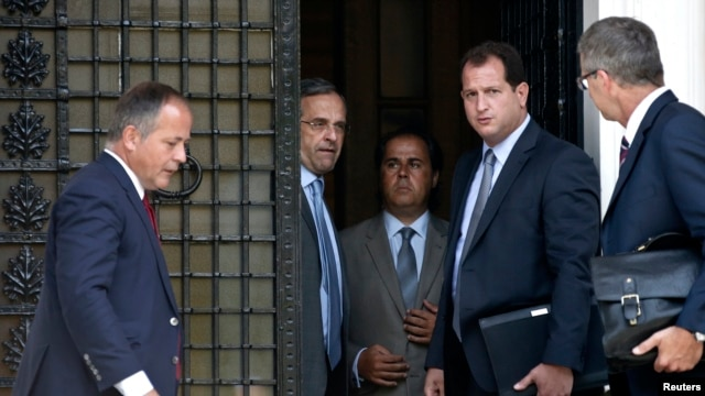 European Central Bank Executive Board member Benoit Coeure (L), Greece's Prime Minister Antonis Samaras (2nd L) and European Central Bank Mission Chief for Greece Klaus Masuch (R) talk after a meeting at the Prime minister's office in Athens, August 28, 2014.