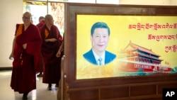 西藏拉萨一所寺庙的喇嘛走过习近平的画像屏风。(2021年5月31日)