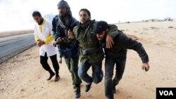 Pemberontak Libya mengangkat seorang rekan mereka yang cedera akibat serangan pasukan Gadhafi di Ras Lanuf, Kamis (10/3).