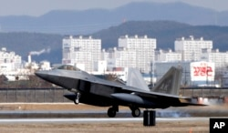 FILE - One of four U.S. F-22 stealth fighters lands at Osan Air Base in Pyeongtaek, South Korea, Feb. 17, 2016. Four U.S. F-22 stealth fighters flew over South Korea in a show of power against North Korea.