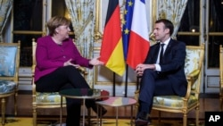 FILE - France's President Emmanuel Macron, right, and German Chancellor Angela Merkel, talk during their meeting, at the Elysee Palace, in Paris, Jan. 19, 2018.