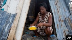 19-year-old Nathanaelle Bernard, who is 7 months pregnant, cooks an omelet in a makeshift hut she is sharing with five members of her extended family, in Coteaux, Haiti, Nov. 1, 2016. Hundreds of thousands of people in southern Haiti are facing food shortages three months after Hurricane Matthew.
